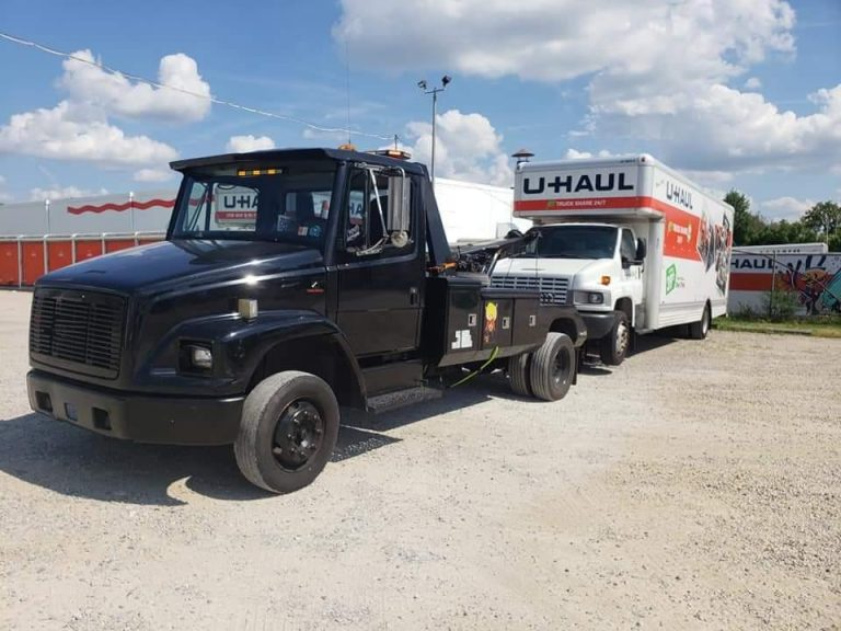 Picture of a tow truck towing a medium duty box truck.